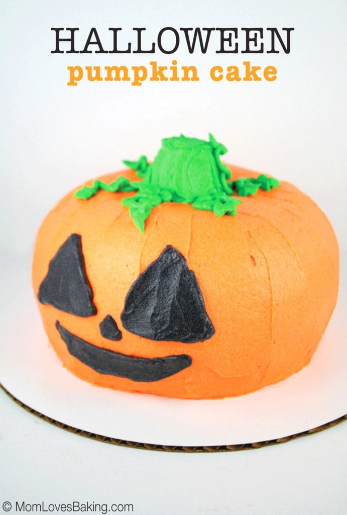 Cake shaped like a pumpkin and frosted with orange icing, green stem