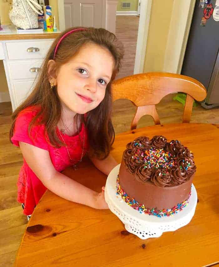Little girl with chocolate birthday cake