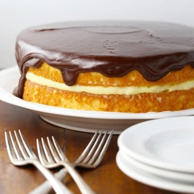 Boston cream pie birthday cake with plates and forks