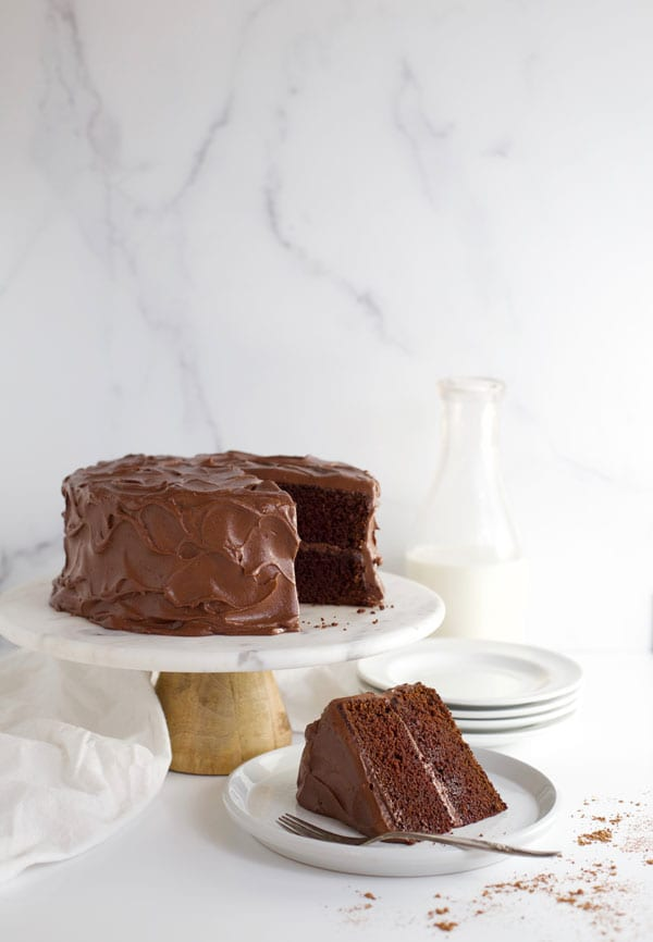 Chocolate fudge cake on cakestand with slice of cake
