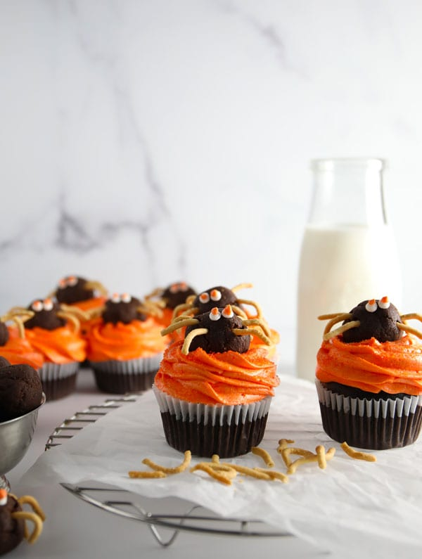 Chocolate cupcakes with vanilla buttercream frosting colored orange for Halloween topped with a chocolate truffle spider with chow mein noodle legs.