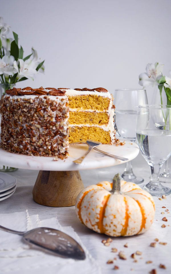 Pumpkin spice pecan layer cake with cream cheese frosting on cake stand