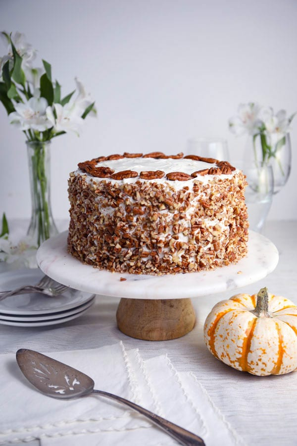 Pumpkin spice pecan layer cake with cream cheese frosting covered with chopped pecans recipe