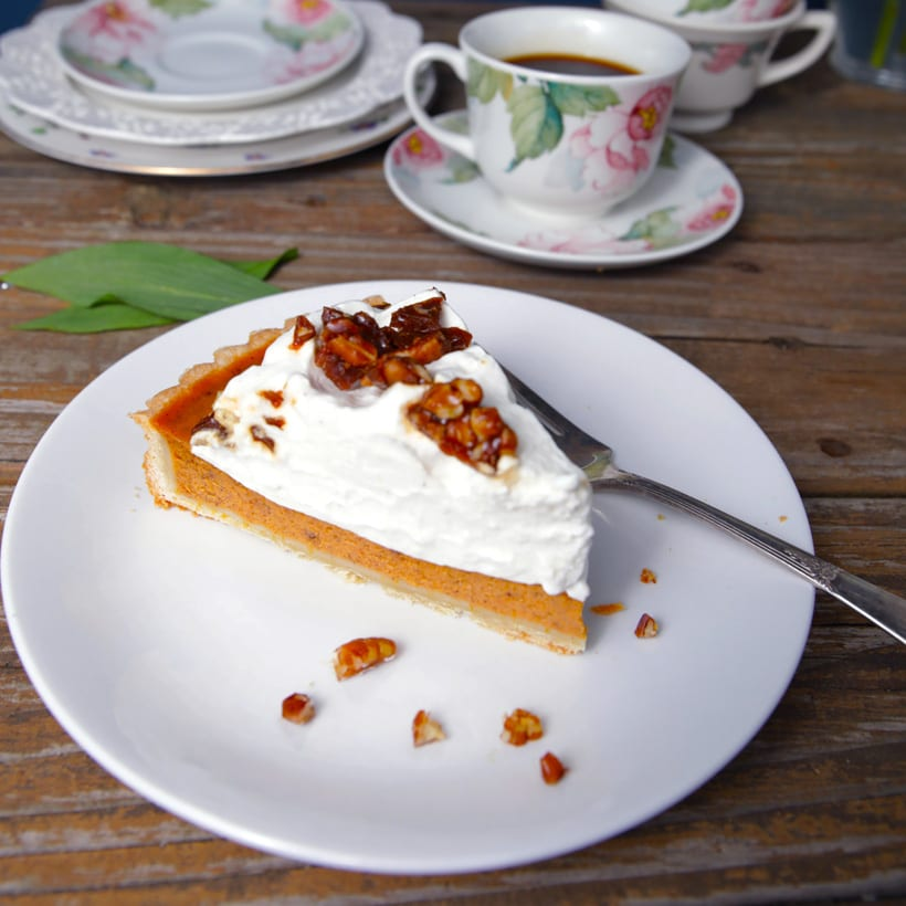 Slice of pumpkin pie with whipped cream and pecan toffee
