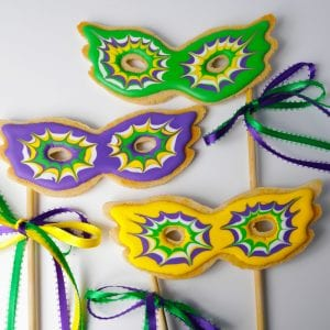 Mardis gras mask cookies on a stick in green purple yellow