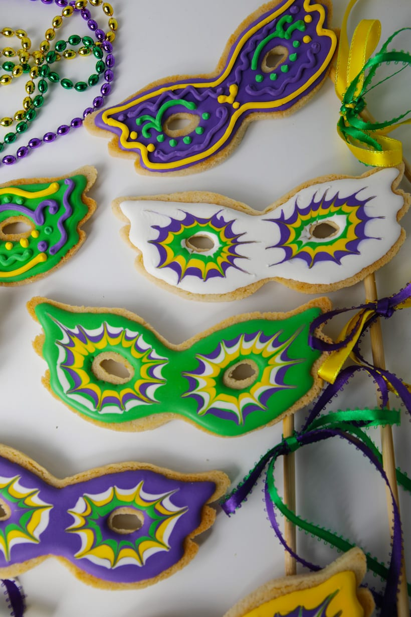 Royal icing decorated mardis gras mask sugar cookies on a stick