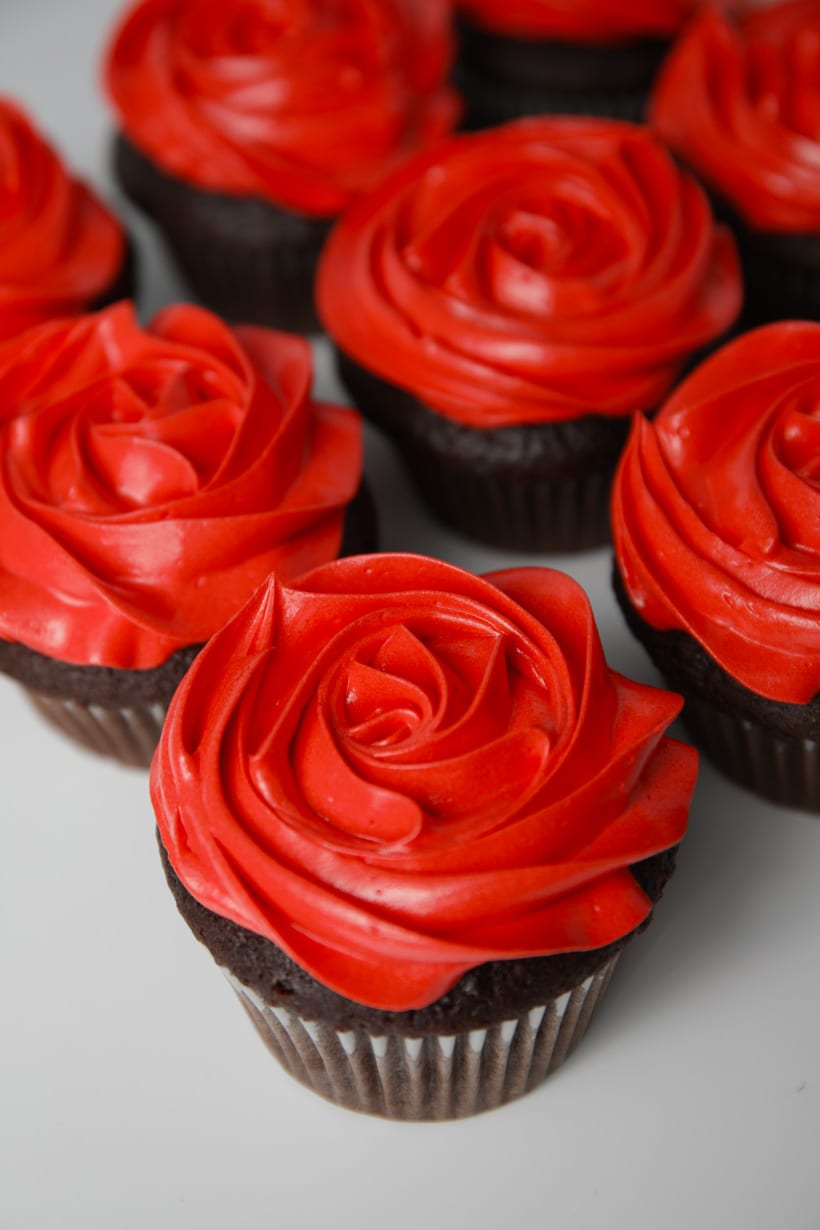 Red buttercream roses on chocolate cupcakes