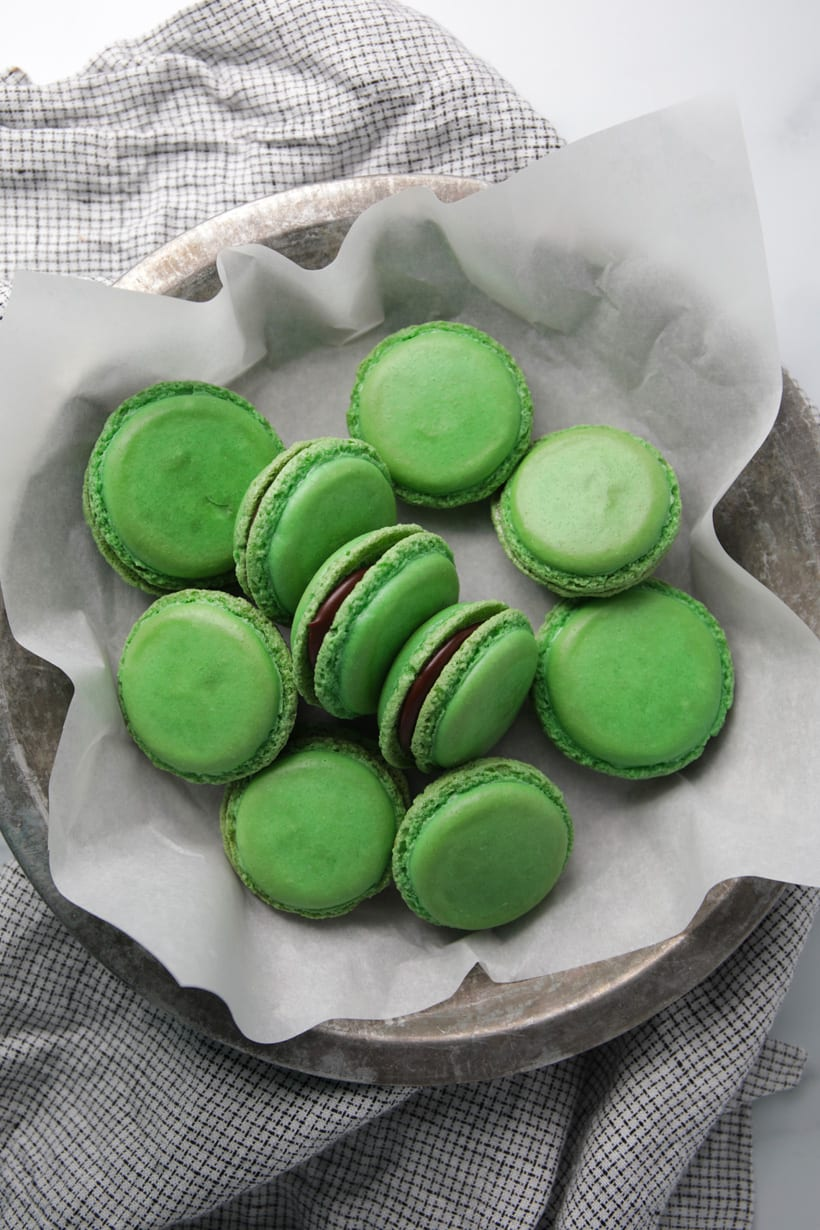 Mint chocolate filled green macaron shells in pie plate